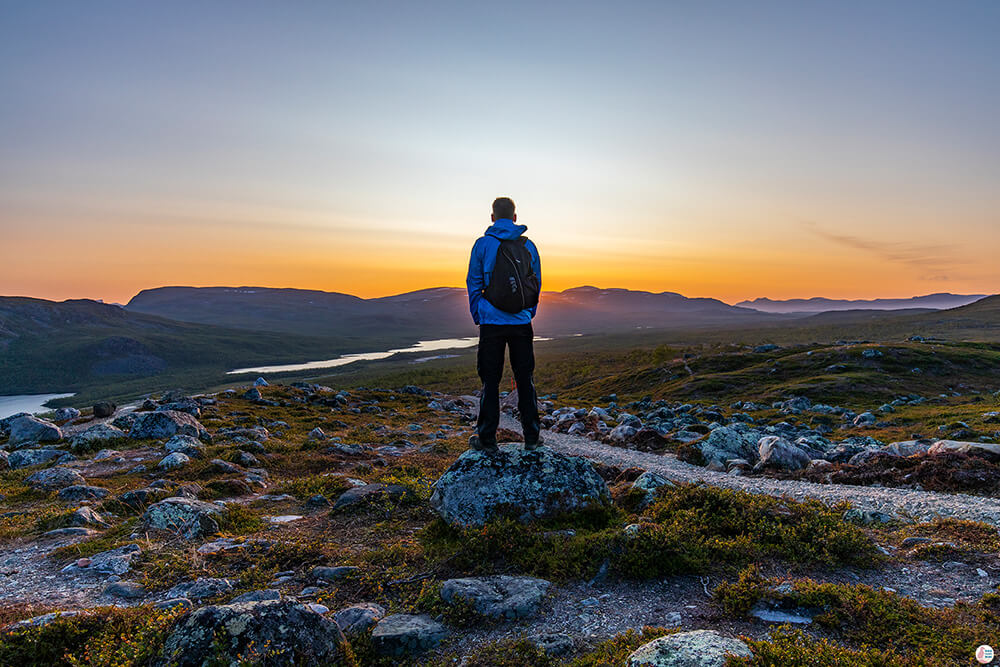 Man admiring the sunset on Saana hiking trail in Kilpisjärvi, Enontekiö, Lapland, Finland
