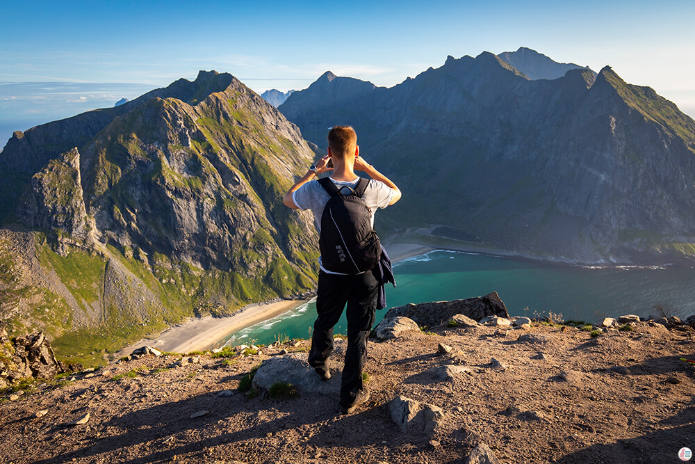Tourist taking picture at Kvalvika beach viewpoint, Ryten hiking trail, Moskenesøya, Lofoten, Norway